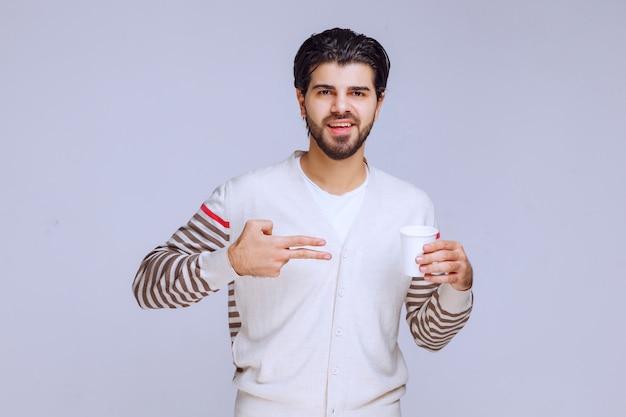 Mężczyzna w białej koszuli trzyma filiżankę kawy.