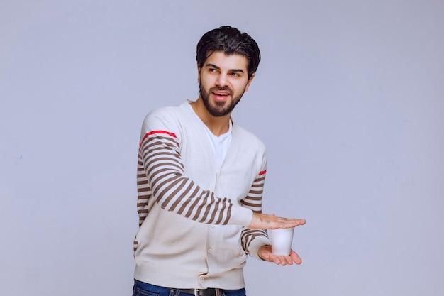 Mężczyzna w białej koszuli trzyma jednorazową filiżankę kawy.