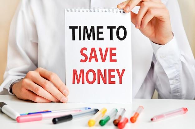 Mężczyzna w białej koszuli trzyma kartkę z napisem: czas na zaoszczędzenie pieniędzy