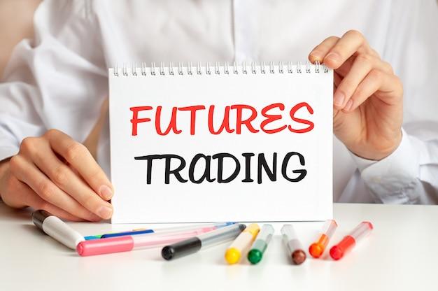 Mężczyzna w białej koszuli trzyma kartkę z napisem: futures trading