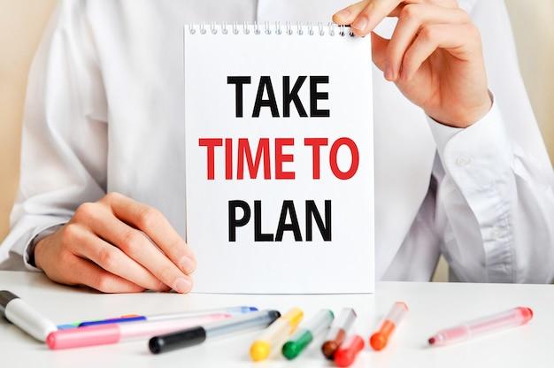 Mężczyzna w białej koszuli trzyma kartkę z napisem: poświęć trochę czasu na planowanie.