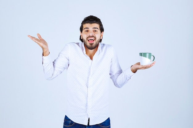 Mężczyzna w białej koszuli trzyma kubek i wygląda na zaskoczony.