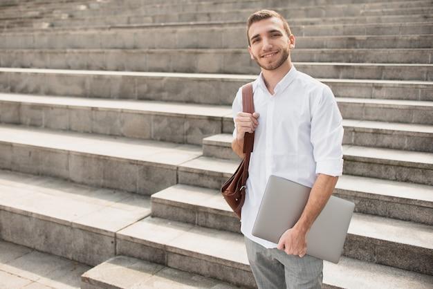 Mężczyzna w białej koszuli trzyma laptopa i uśmiecha się do kamery