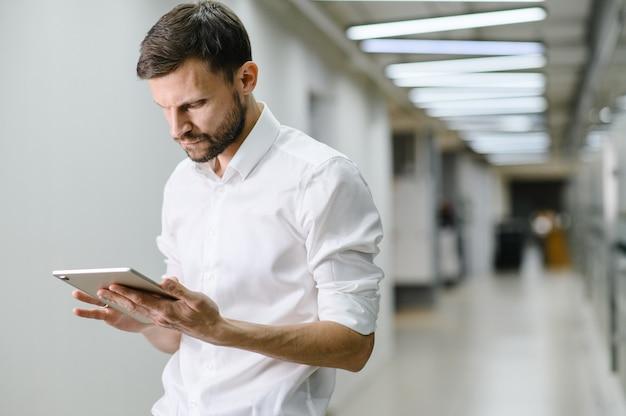 Mężczyzna w białej koszuli trzyma tablet i uśmiecha się w biurze człowiek biznesu na tle biura wysokiej jakości zdjęcie