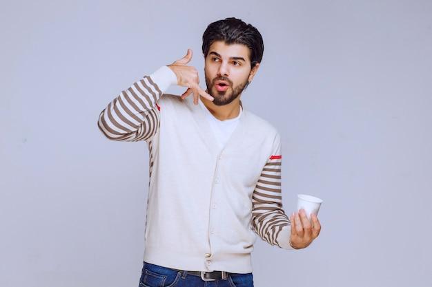 Mężczyzna w białej koszuli, trzymając filiżankę kawy i prosząc o telefon.