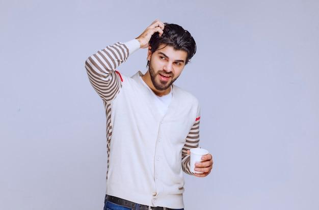 Mężczyzna w białej koszuli, trzymając i pijąc filiżankę kawy.
