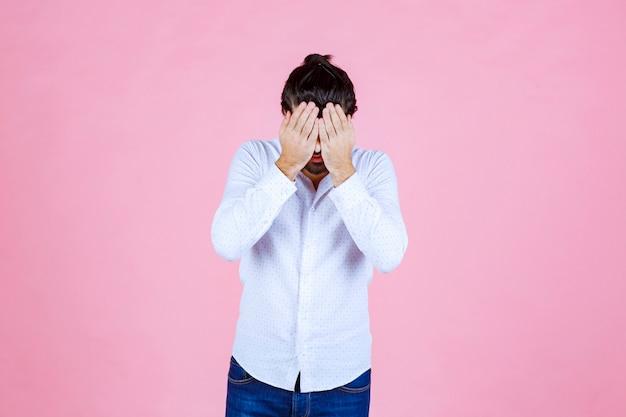 Mężczyzna w białej koszuli trzymający się za głowę z powodu bólu głowy.