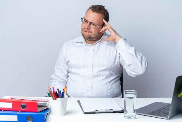 Mężczyzna w białej koszuli w okularach, patrząc na bok, zdezorientowany i bardzo niespokojny, siedzący przy stole z folderami biurowymi laptopa i schowkiem na białej ścianie, pracujący w biurze