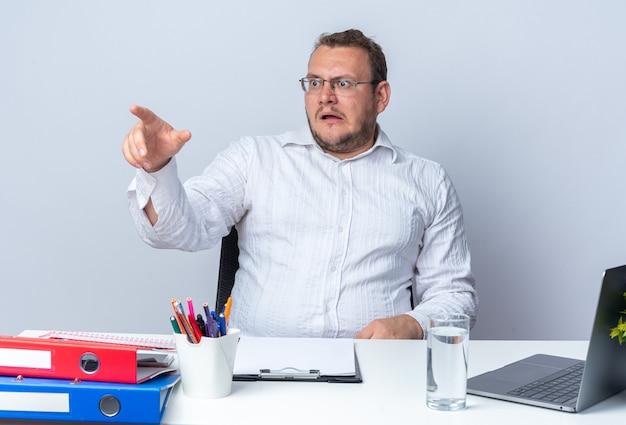 Mężczyzna w białej koszuli w okularach, patrząc na bok, zmartwiony, wskazując palcem wskazującym na coś, co siedzi przy stole z folderami biurowymi laptopa i schowkiem na białym