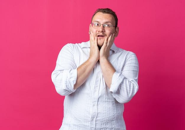 Mężczyzna w białej koszuli w okularach, patrzący na bok zdumiony i zaskoczony, stojący nad różową ścianą