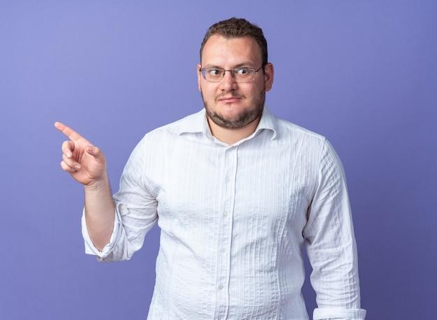 Mężczyzna w białej koszuli w okularach patrzący w bok zdezorientowany, wskazując palcem wskazującym w bok