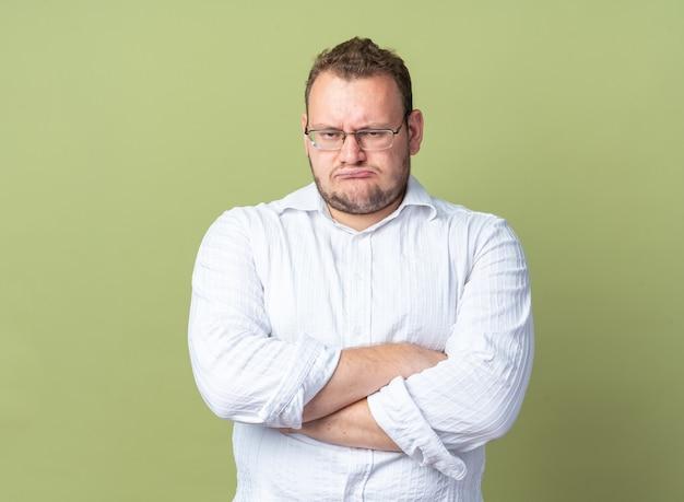 Mężczyzna w białej koszuli w okularach, patrzący ze zmarszczoną twarzą ze skrzyżowanymi rękami