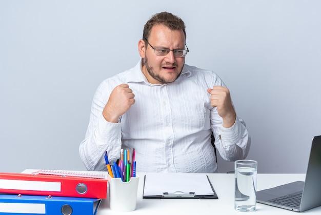 Mężczyzna w białej koszuli w okularach siedzi przy stole z folderami biurowymi i schowkiem, patrząc na ekran laptopa, szczęśliwy i podekscytowany, zaciskając pięści nad białą ścianą, pracujący w biurze