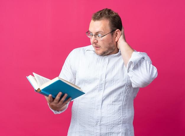 Mężczyzna w białej koszuli w okularach trzymający książkę patrząc na nią zdumiony i zaskoczony stojąc na różowo