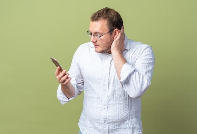 Mężczyzna w białej koszuli w okularach trzymający smartfona patrzący na niego zdezorientowany i bardzo niespokojny stojący na zielono