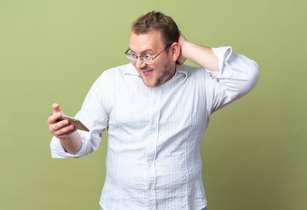 Mężczyzna w białej koszuli w okularach trzymający smartfona patrzący na niego zdumiony i zaskoczony stojąc nad zieloną ścianą