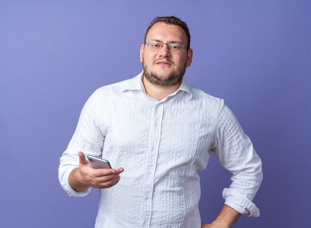 Mężczyzna w białej koszuli w okularach trzymający smartfona uśmiechnięty pewnie stojący nad niebieską ścianą