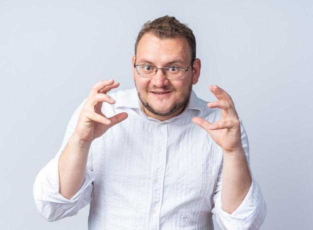 Mężczyzna w białej koszuli w okularach, uśmiechający się radośnie z podniesionymi rękami