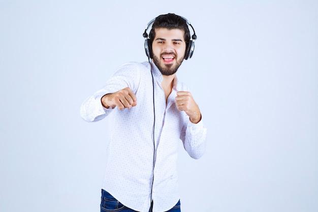 Mężczyzna w białej koszuli w słuchawkach i słuchający muzyki