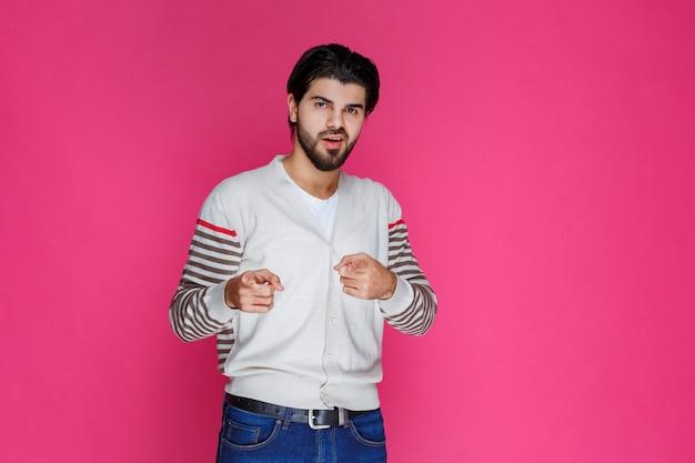 Mężczyzna w białej koszuli, wskazując i przedstawiając kogoś z przodu.