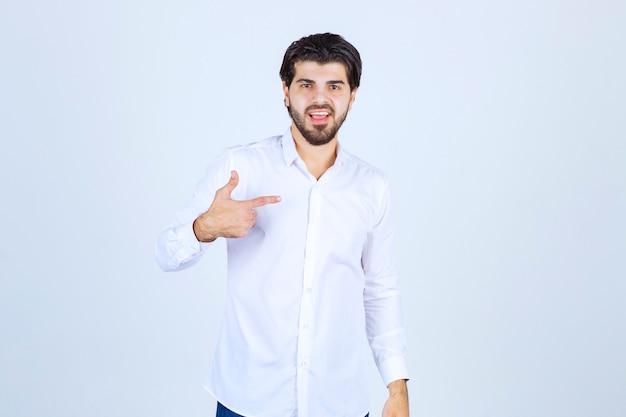 Mężczyzna w białej koszuli, wskazując na coś po prawej stronie.