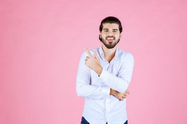 Mężczyzna w białej koszuli, wskazując na lewą stronę.