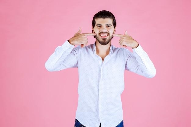 Mężczyzna w białej koszuli, wskazując na swój uśmiech.