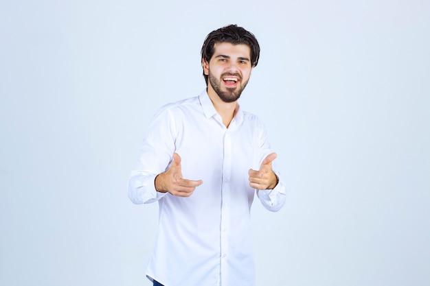 Mężczyzna w białej koszuli, wskazując na swojego kolegę.