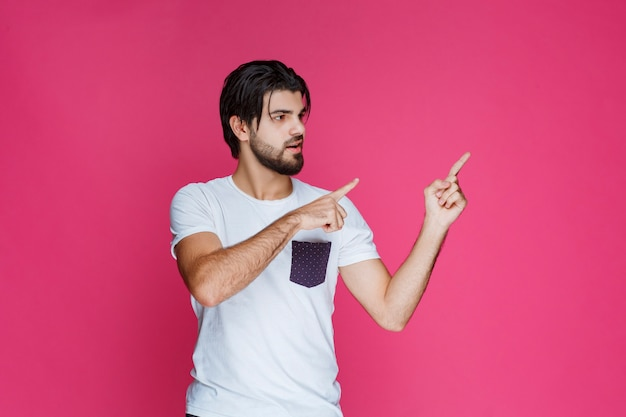 Mężczyzna w białej koszuli wskazujący gdzieś i przedstawiający kogoś lub po prostu wskazujący kierunek.