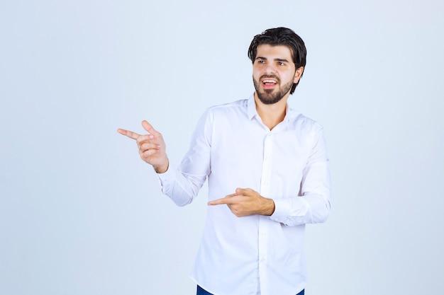 Mężczyzna w białej koszuli wskazujący gdzieś po lewej stronie z emocjami twarzy.