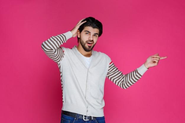 Mężczyzna w białej koszuli wskazuje i przedstawia coś po prawej stronie.