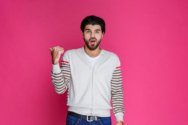 Mężczyzna w białej koszuli wskazuje i przedstawia coś z tyłu.