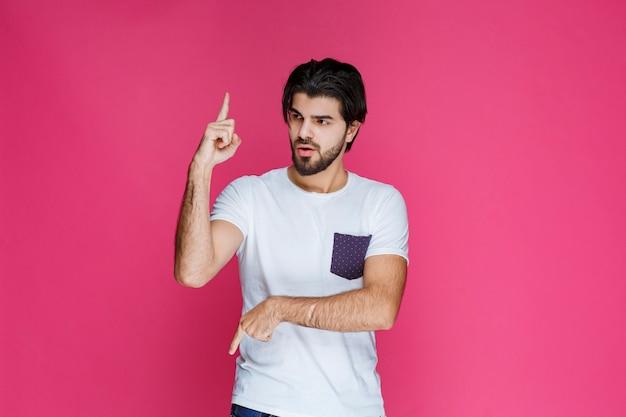 Mężczyzna w białej koszuli wskazuje na coś palcem wskazującym.