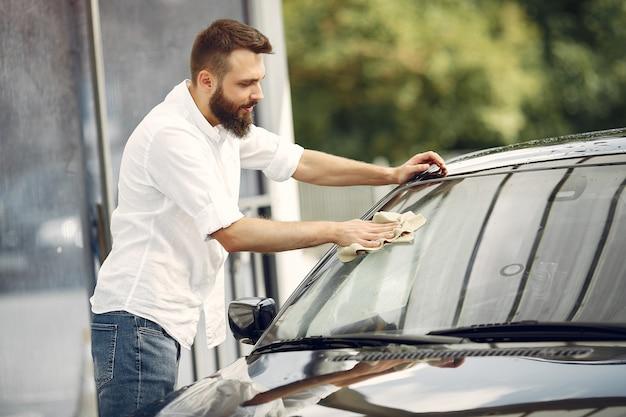 Mężczyzna w białej koszuli wyciera samochód w myjni samochodowej
