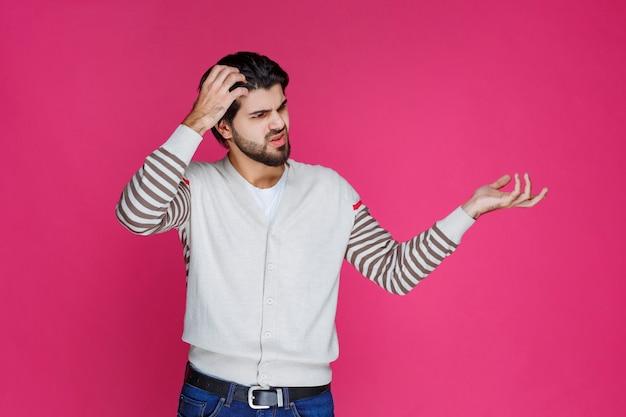 Mężczyzna w białej koszuli wygląda na zagubionego i zagubionego.