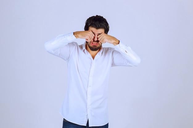 Mężczyzna w białej koszuli wygląda na zaspanego lub smutnego.
