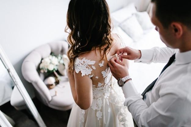 Mężczyzna w białej koszuli z krawatem i zegarkiem zapina guziki gorsetu sukienki. panna młoda w sukni ślubnej z koronki stojącej w domu.