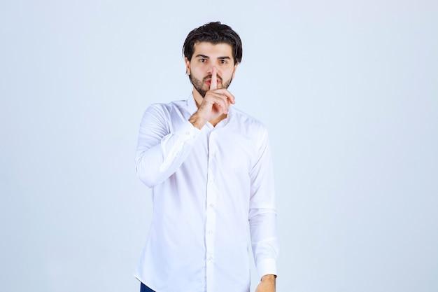 Mężczyzna w białej koszuli z prośbą o ciszę.