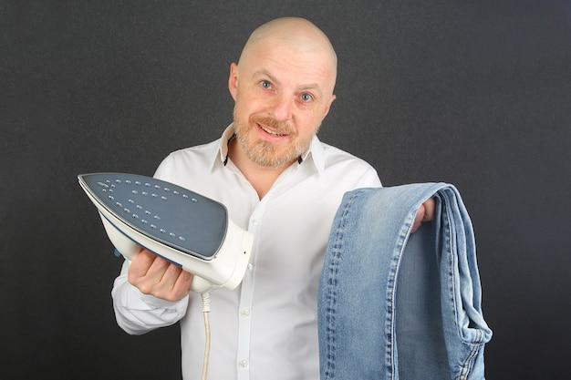 Mężczyzna w białej koszuli z żelazkiem do prasowania i dżinsami w rękach