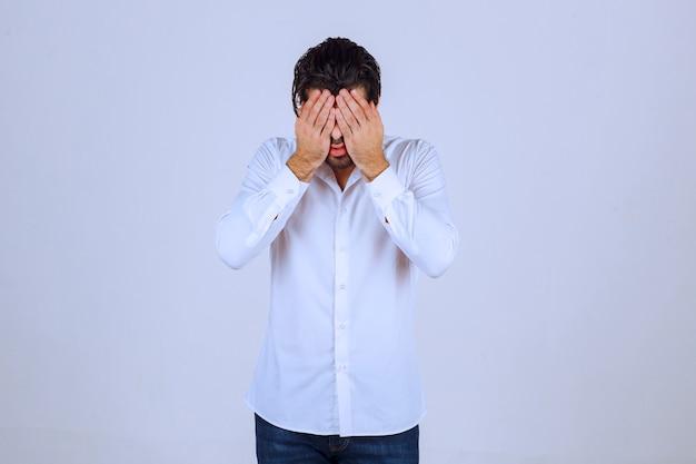 Mężczyzna w białej koszuli zasłania twarz, czuje się smutny i boli go głowa.