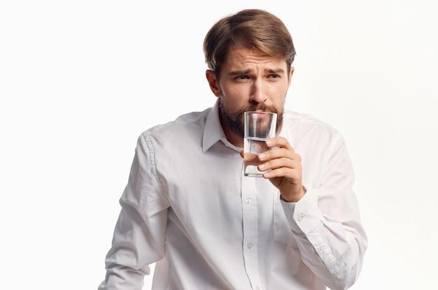 Mężczyzna w białej koszuli ze szklanką wody w ręku promocja przycięty widok.