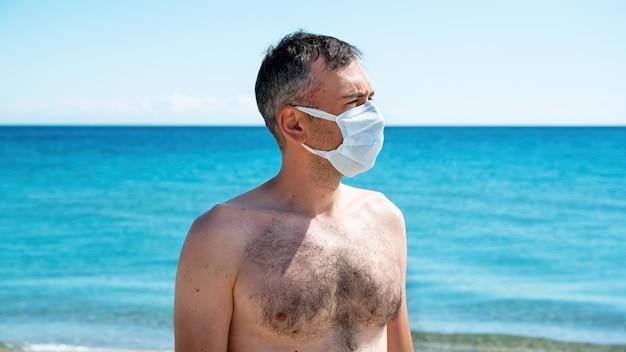 Mężczyzna w białej masce medycznej na morzu
