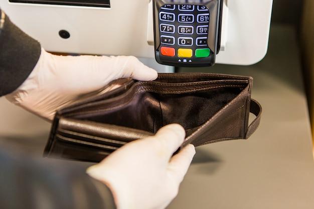 Mężczyzna w białych lateksowych rękawiczkach, trzymając pustą torebkę. brązowa torebka bez pieniędzy. problemy finansowe