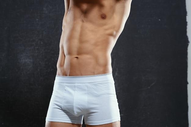 Mężczyzna w białych majtkach napompował ciało do ćwiczeń fitness w kulturystyce