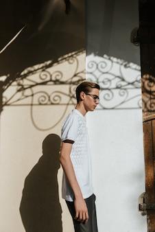 Mężczyzna w białych polo i szarych spodniach pozuje na ulicy, by reklamować męskie ubrania.