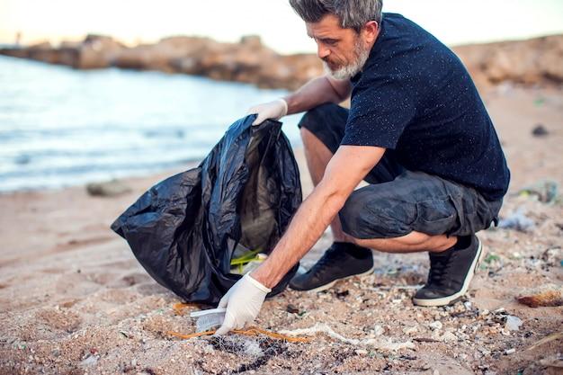 Mężczyzna w białych rękawiczkach i dużym czarnym opakowaniu zbierającym śmieci na plaży. koncepcja ochrony środowiska i zanieczyszczenia planety