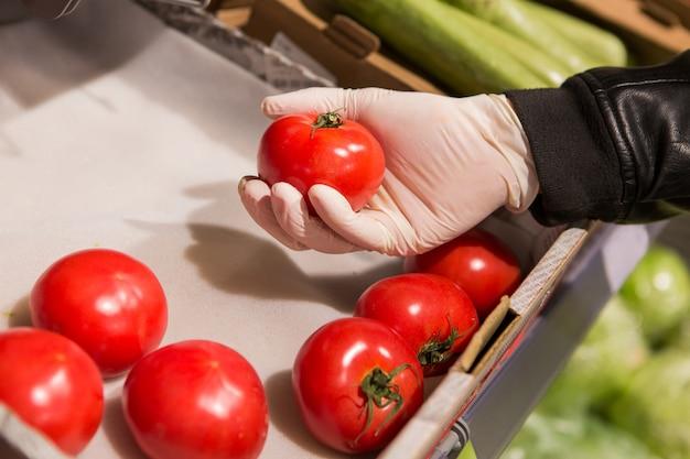Mężczyzna w białych rękawiczkach w sklepie kupuje jedzenie. mężczyzna trzyma pomidoru w jego rękach