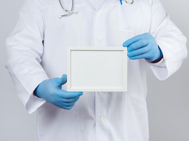 Mężczyzna w białym fartuchu i niebieskich lateksowych rękawiczkach trzyma pustą białą ramkę na napis