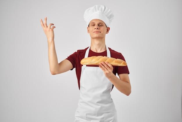 Mężczyzna w białym fartuchu z bochenkiem w rękach profesjonalnego wypiekacza