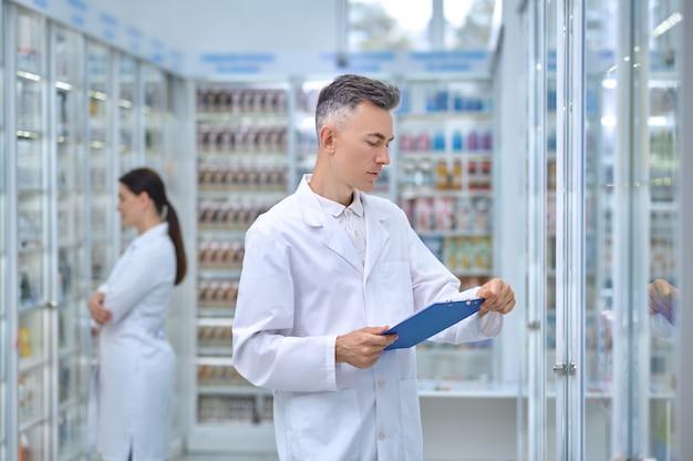Mężczyzna w białym fartuchu z folderem w aptece